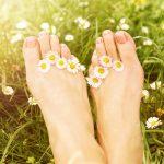 Füße mit Gänseblümchen in Sommerwiese