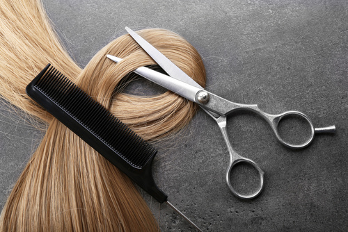 Hairdresser's scissors with comb and strand of blonde hair on gr